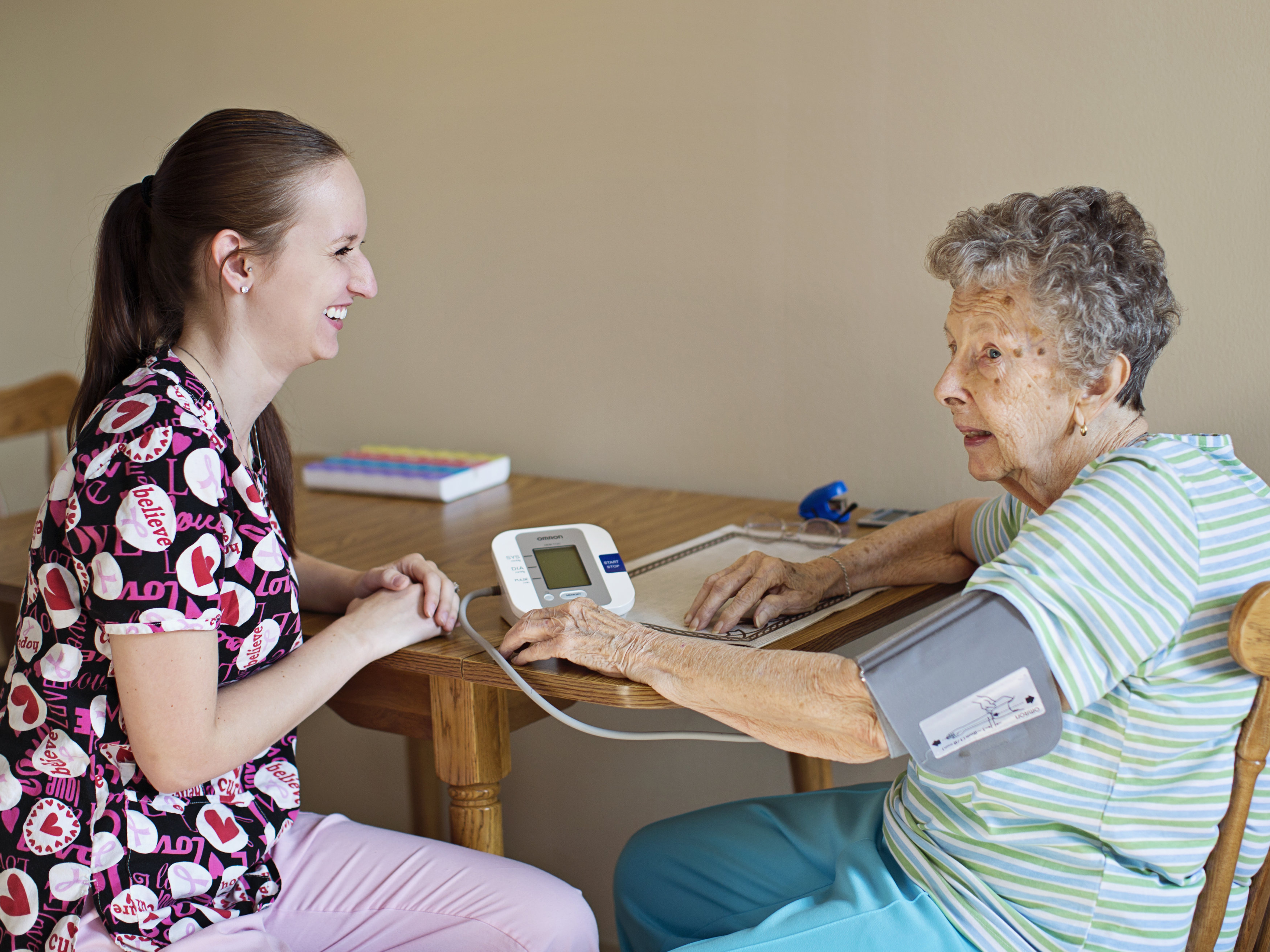 In-Home Health Caregiver checking blood pressure of elder care patient.