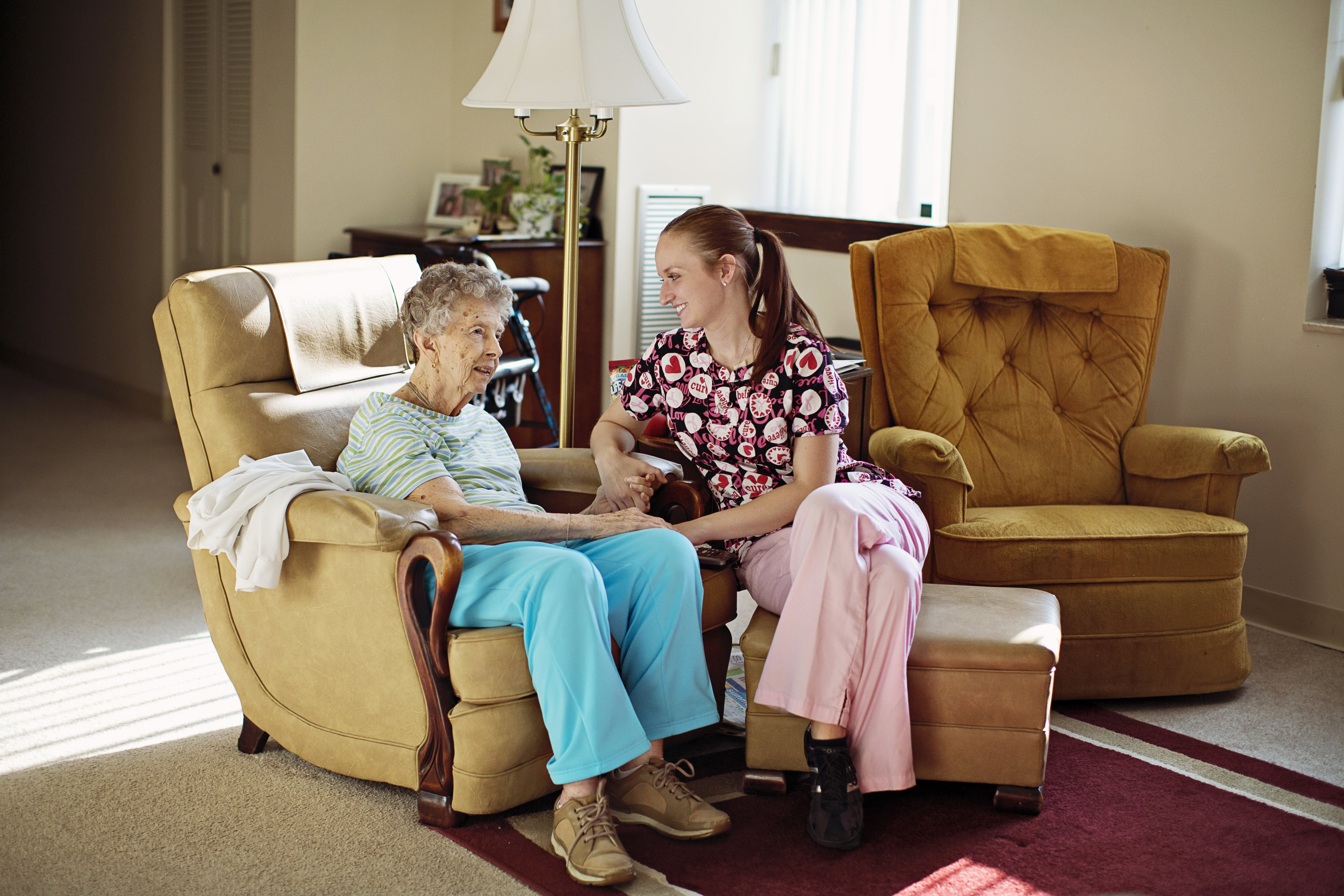Home Health Caregiver sitting & holding hands of elderly companion care patient.