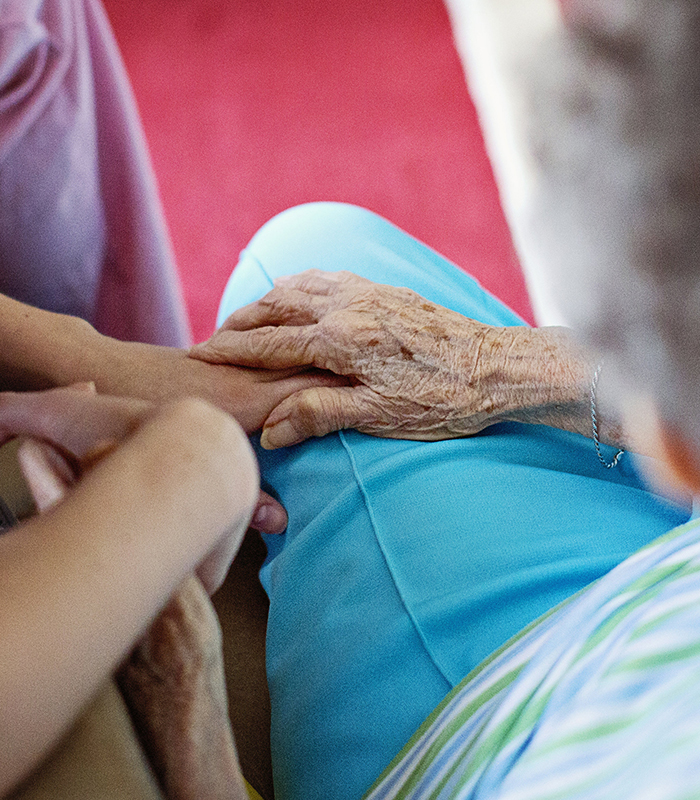 Home Caregiver sitting with elderly in-home care patient.