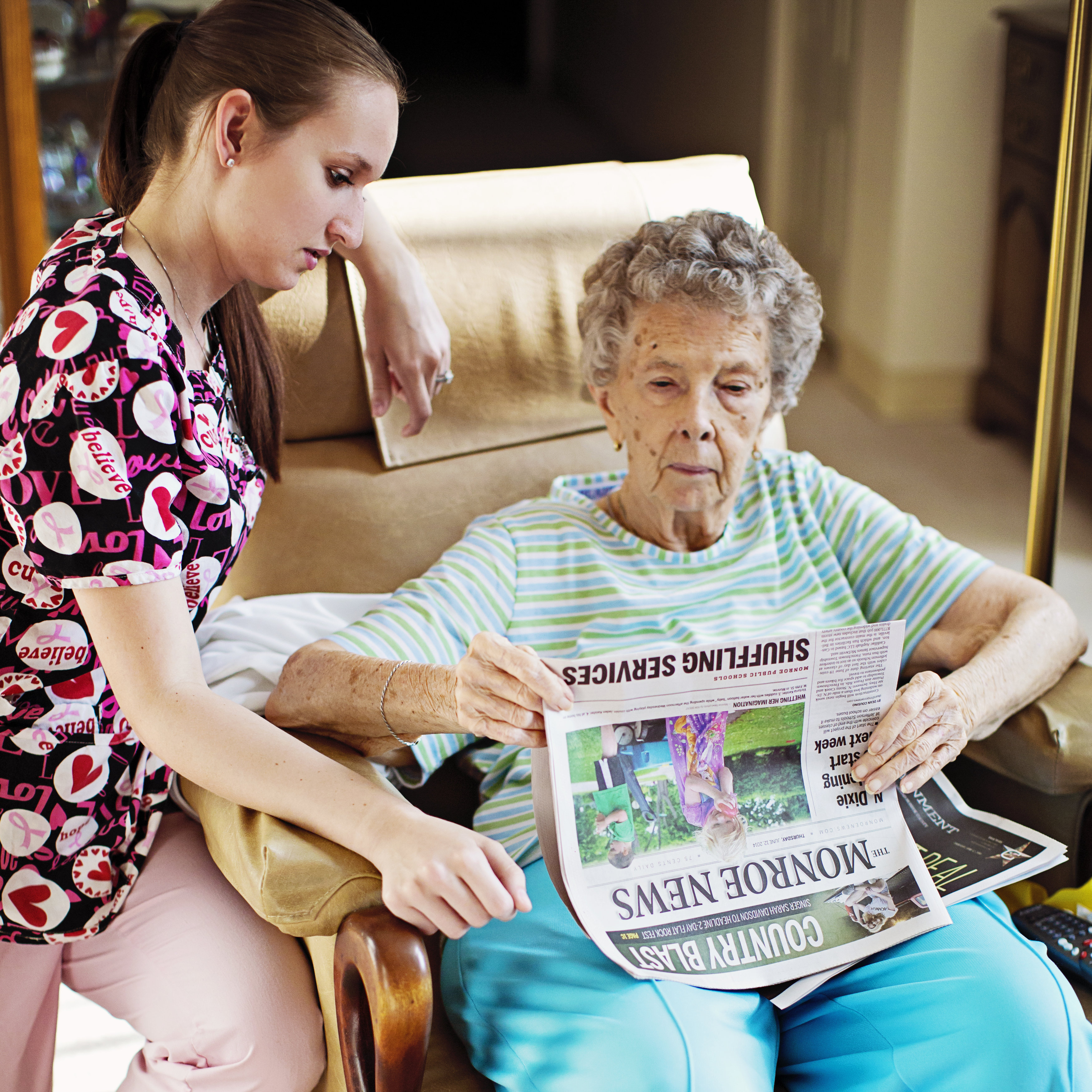 Home Caregiver sitting with elderly patient reading a newspaper.