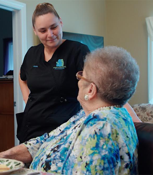 Home Health Caregiver with patient sitting down.